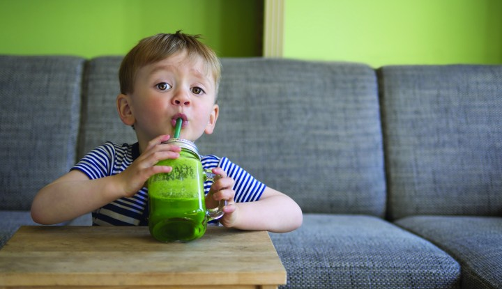 adorable toddler drinking a green smoothie
