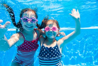 Two little girls deftly swim underwater in pool